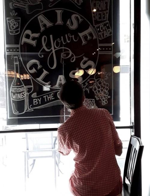 Alison Garwood-Jones painting designs on a window